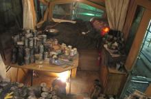 View inside the trailer, in the foreground piles of food-cans. A blanket sized piece of lead covers the bed.